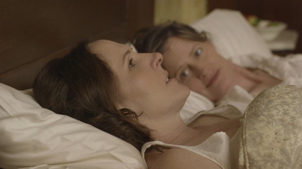 Emily (Molly Shannon) and Susan (Susan Ziegler) lying in bed - WILD NIGHTS WITH EMILY - Courtesy of Greenwich Entertainment